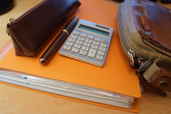 オレンジ色のクリアファイルに計算機が乗っている写真