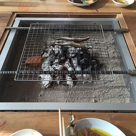 囲炉裏の炭火でシシャモを炙っている画像