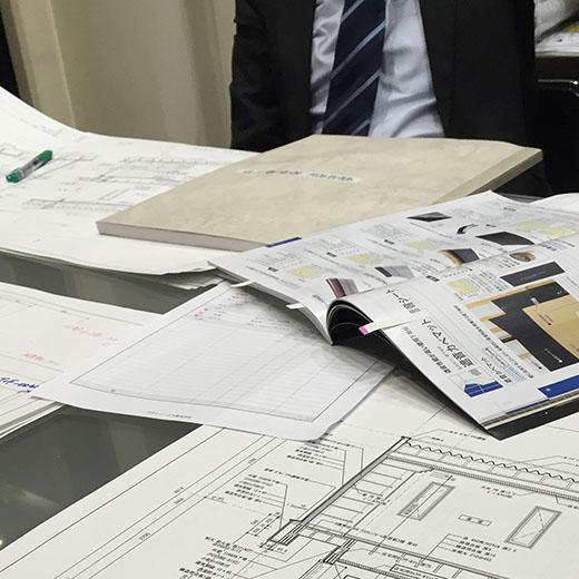 新築物件の建築図面と会議中の画像