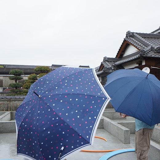 傘をさして現場立ち会いをしている写真