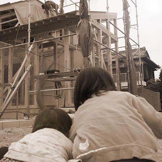 家が建つのを見ている姉妹の写真