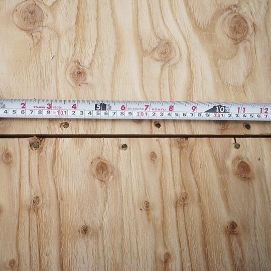 構造用合板の釘打ちピッチを計測している写真