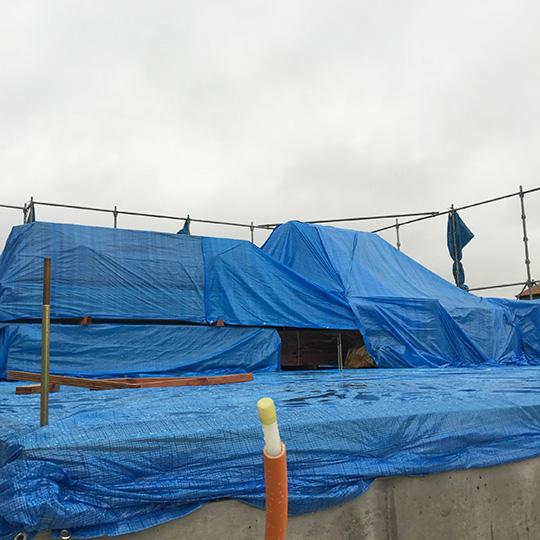 ブルーシートを掛けられた構造材の写真