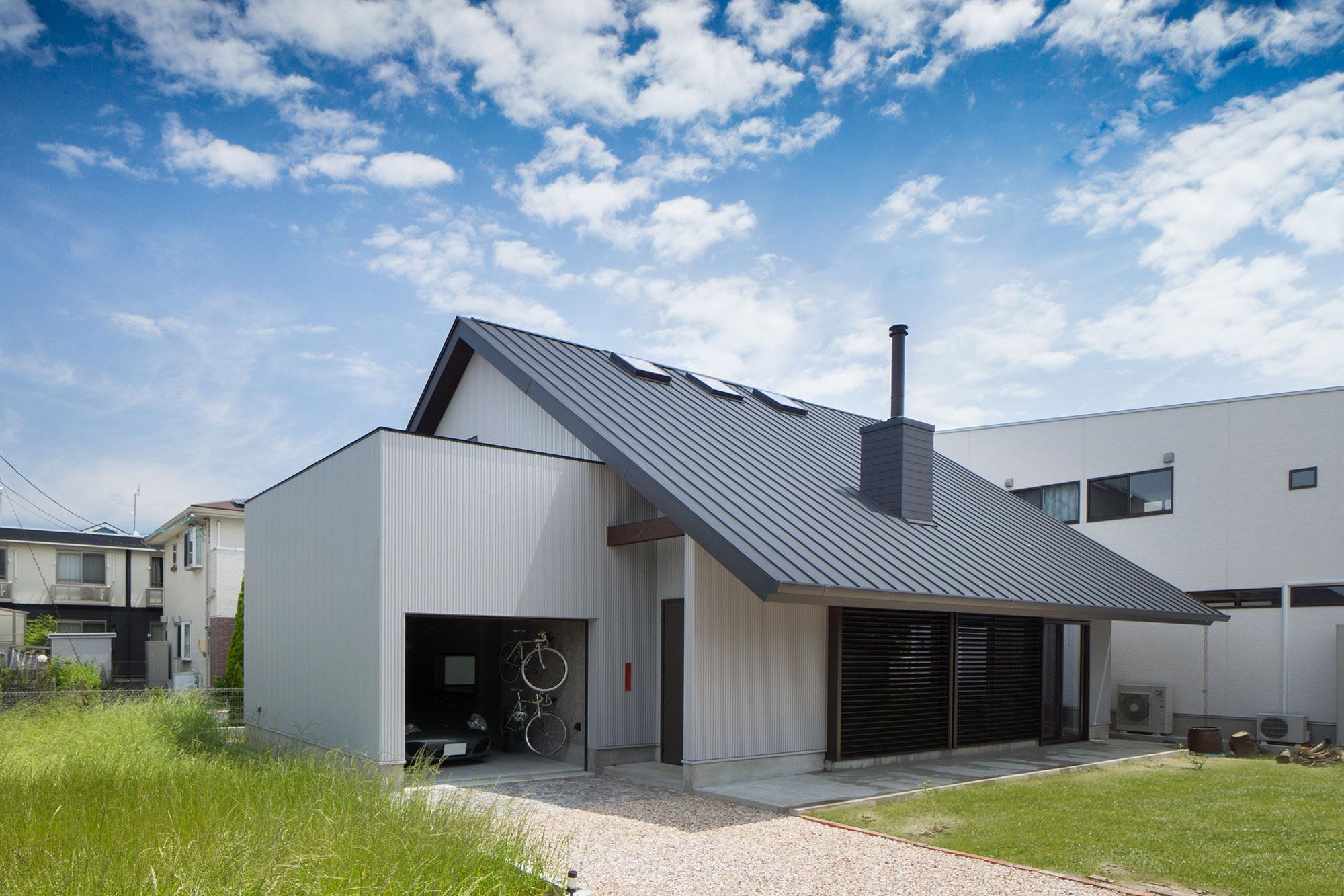 薪ストーブの煙突があるガレージハウスの外観写真