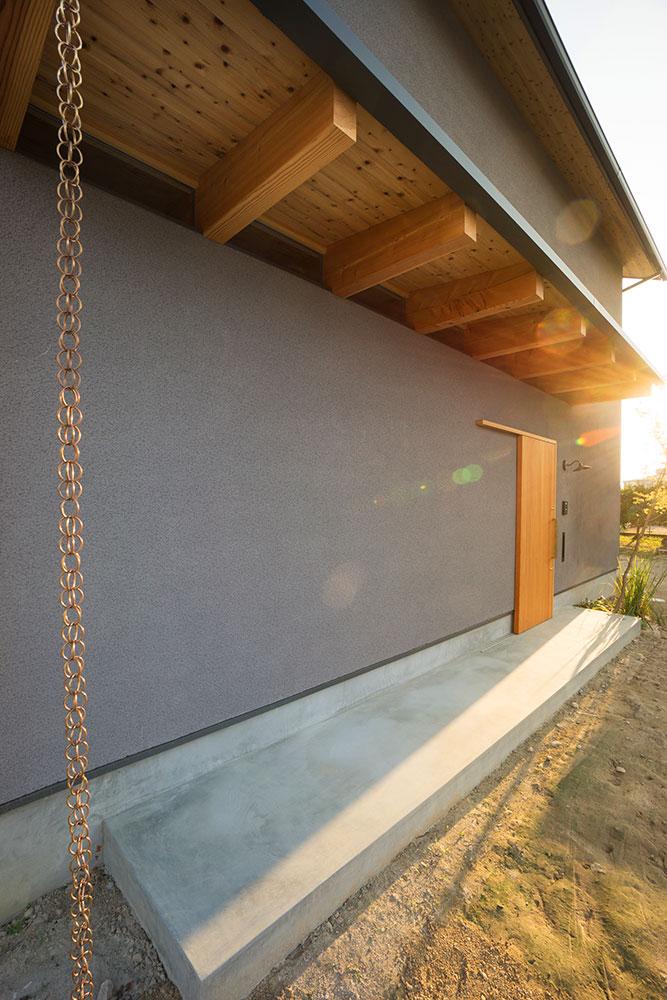 そとん壁の外壁|杉板張りの軒天と鎖樋の写真